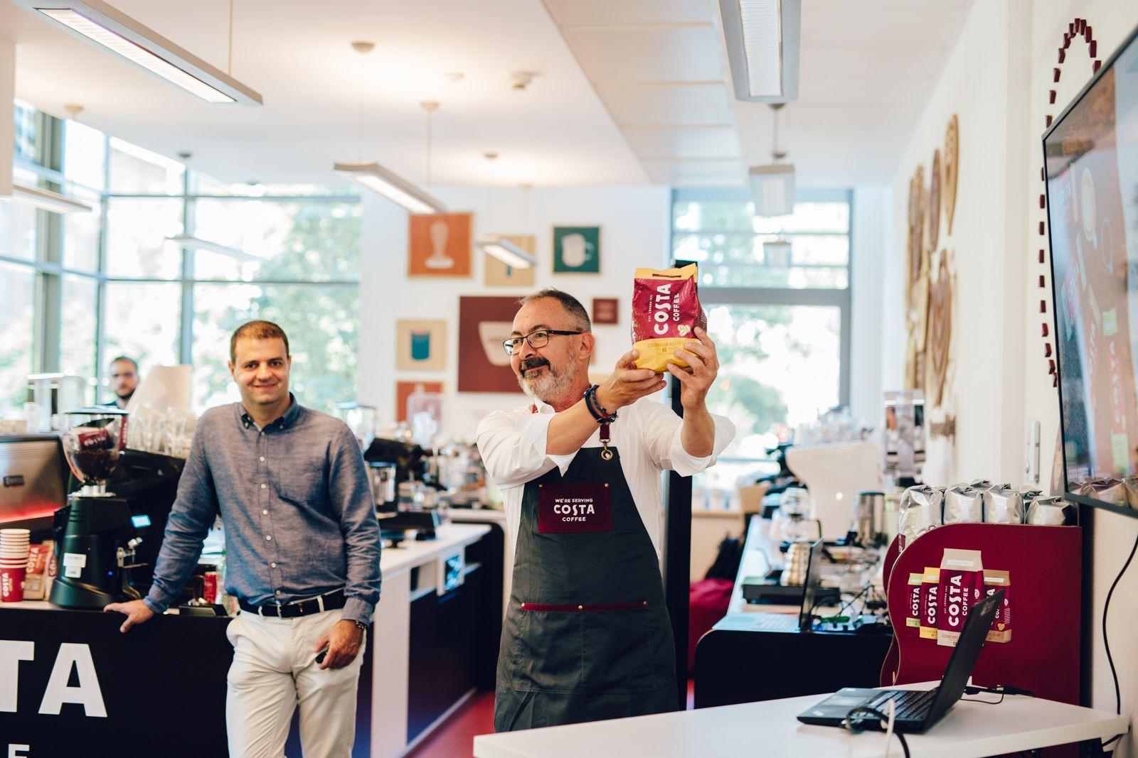 Gávris Iván a magasba emelve mutatja a COSTA szemes kávéját, Vajda Mártonnal mögötte.
