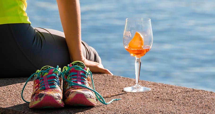 vízparton ülő lány egy pohár aperollal