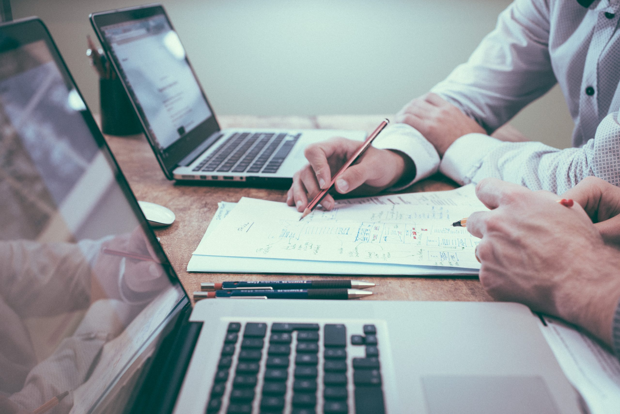 munkahelyen kollégák átbeszélik a feladatot egy íróasztalnál