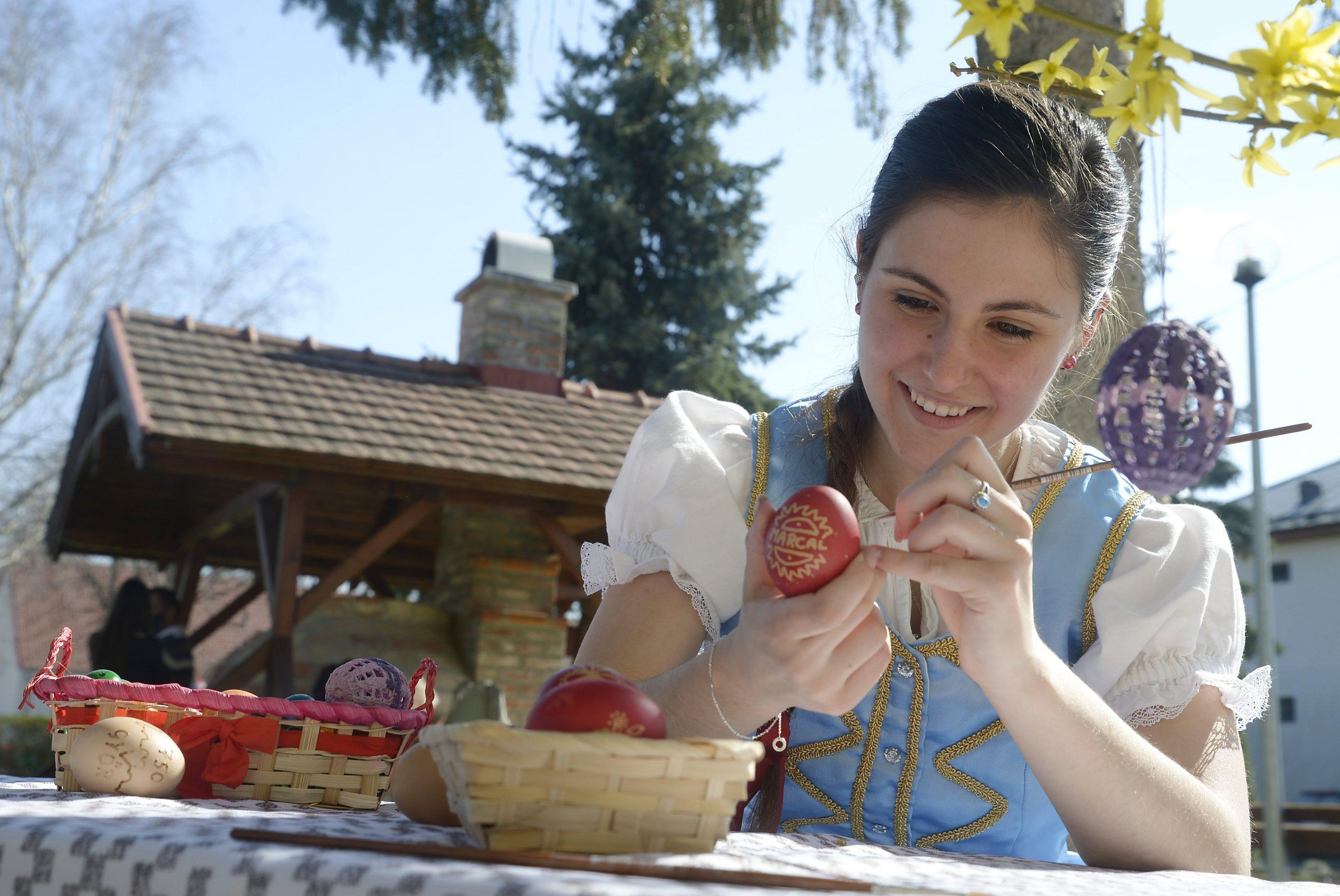 A Marcal Tánc- és Népművészeti Egyesület tagja húsvéti tojást fest a gyírmóti Művelődési Ház udvarán 2021. március 31-én. Hétszázötven darab hímes tojás készül Győr város fennállásának évfordulójára. MTI/Krizsán Csaba