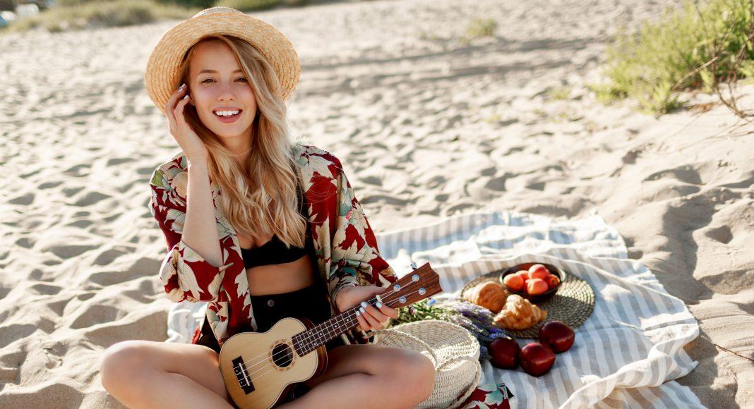 Nő gitárral a tengerparton